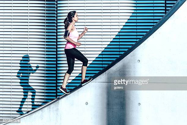 latina sports woman running up on concrete wall in berlin