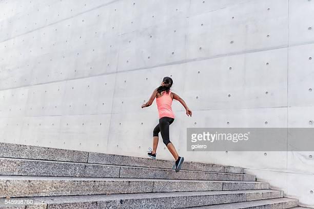 latina sports woman running up stone outdoor stairway