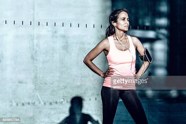 latina sportswoman standing in front of glass facade