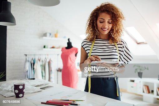 Latina Tailor Using DIgital Tablet In Her Workshop