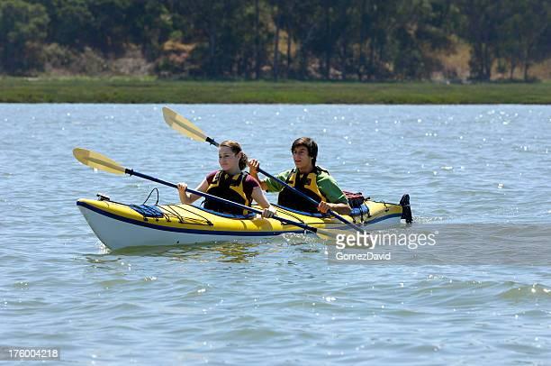 Latino and Caucasian Teenagers Kayaking on Body of Water