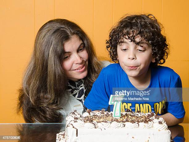 Latino boy with mother blowing candle on cake celebrating his seventh birthday
