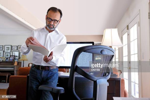Latino Businessman Standing At Desk As He Works From Home