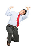 A stressed latino businessman in business clothes on knee using arms pushing up, resisting against crushing imaginary weight, object under heavy stress, feeling pressure. Isolated on white background
