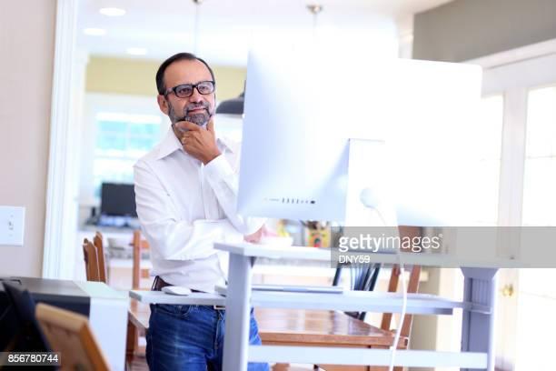 Latino Geschäftsmann arbeitet am Computer-Schreibtisch zu Hause stehen