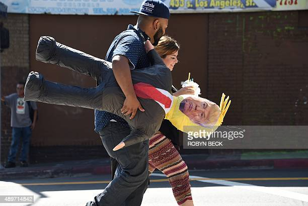 A Latino couple walk with a pinata of Republican presidential candidate Donald Trump September 23 2015 in downtown Los Angeles At the start of his...