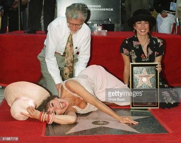 Latino entertainer Rita Moreno lays down next to her star on the Hollywood Walk of Fame as her husband Leonard Gordan and daughter Fernanda Louisa...