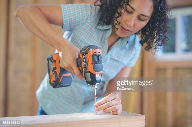 Latino female using a cordless drill to drill screw