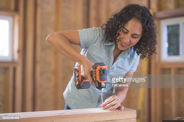Latino female using a cordless screwdriver to screw
