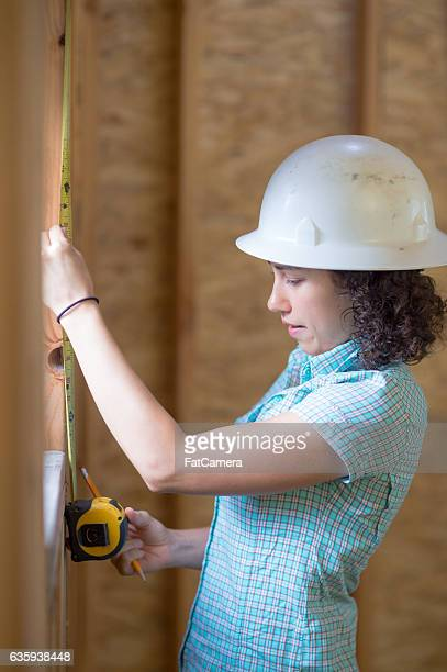 Latino female using a tape measure to check window