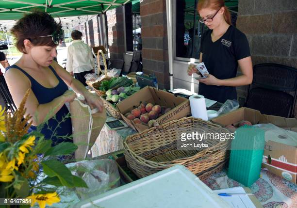 Latisha Sena bags up her fresh peaches she purchased at the Farmer's market at the DHS Richard T Castro Building on July 17 2017 in Denver The...