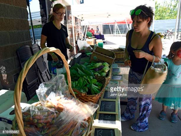 Latisha Sena looks over the fresh vegetables at the Farmer's market at the DHS Richard T Castro Building on July 17 2017 in Denver The farmfresh...