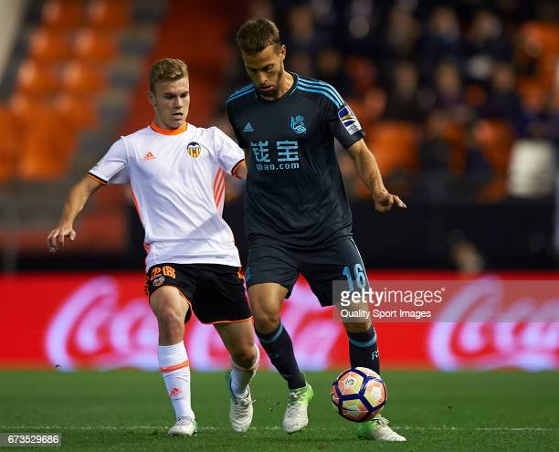 Lato of Valencia competes for the ball with Sergio Canales of Real Sociedad during the La Liga match between Valencia CF and Real Sociedad de Futbol...