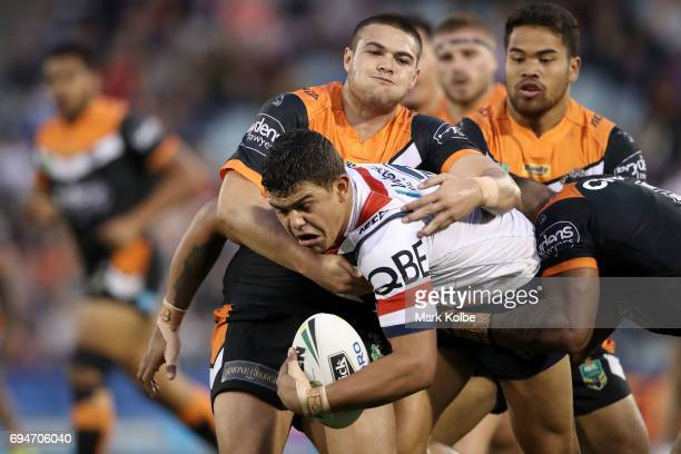 Latrell Mitchell of the Roosters is tackled during the round 14 NRL match between between the Wests Tigers and the Sydney Roosters at Campbelltown...