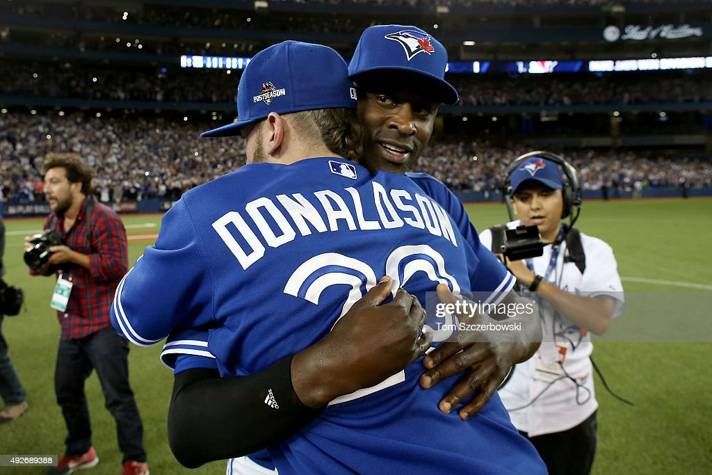 LaTroy Hawkins and Josh Donaldson of the Toronto Blue Jays celebrate the 63 win against the Texas Rangers as Ben Revere jumps on top of the pile in...