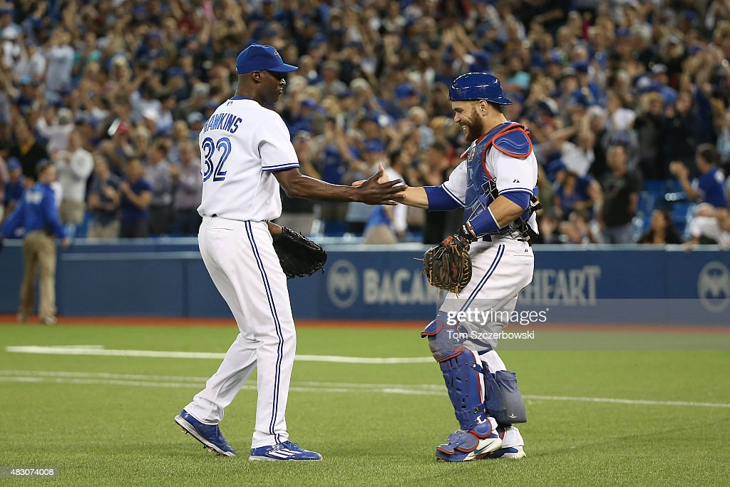 LaTroy Hawkins of the Toronto Blue Jays celebrates a victory with Russell Martin after MLB game action against the Minnesota Twins on August 5 2015...