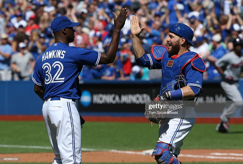 LaTroy Hawkins of the Toronto Blue Jays celebrates their victory with Russell Martin during MLB game action against the Minnesota Twins on August 3...