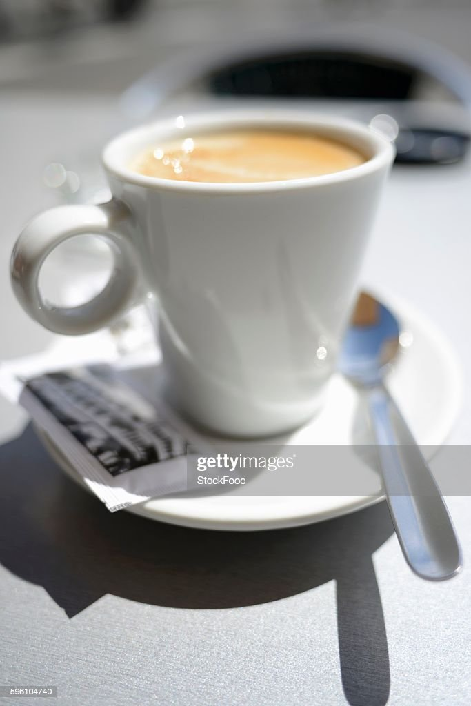 Latte in a white cup with a packet of sugar and a spoon