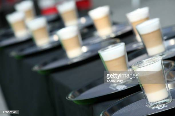 Latte macchiato coffee drinks to be carried on waitress' trays when they will race shortly thereafter sit prior to being carried in competition in...