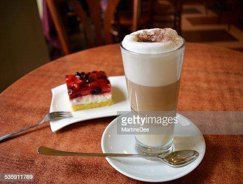 Taza de café con leche y de un Macchiato de vidrio en la torta de fresas : Foto de stock