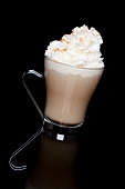 A clear glass filled with coffee is topped off with whipped cream and cinnamon.  Beverage is reflected on glossy surface with black background
