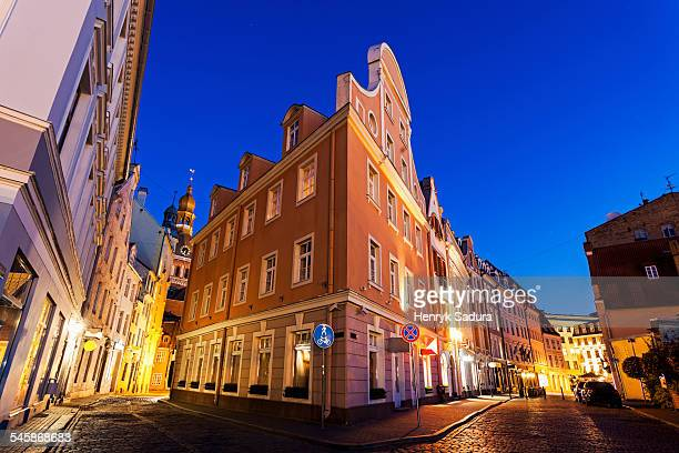 Latvia, Riga, Corner of illuminated building against blue dusk sky