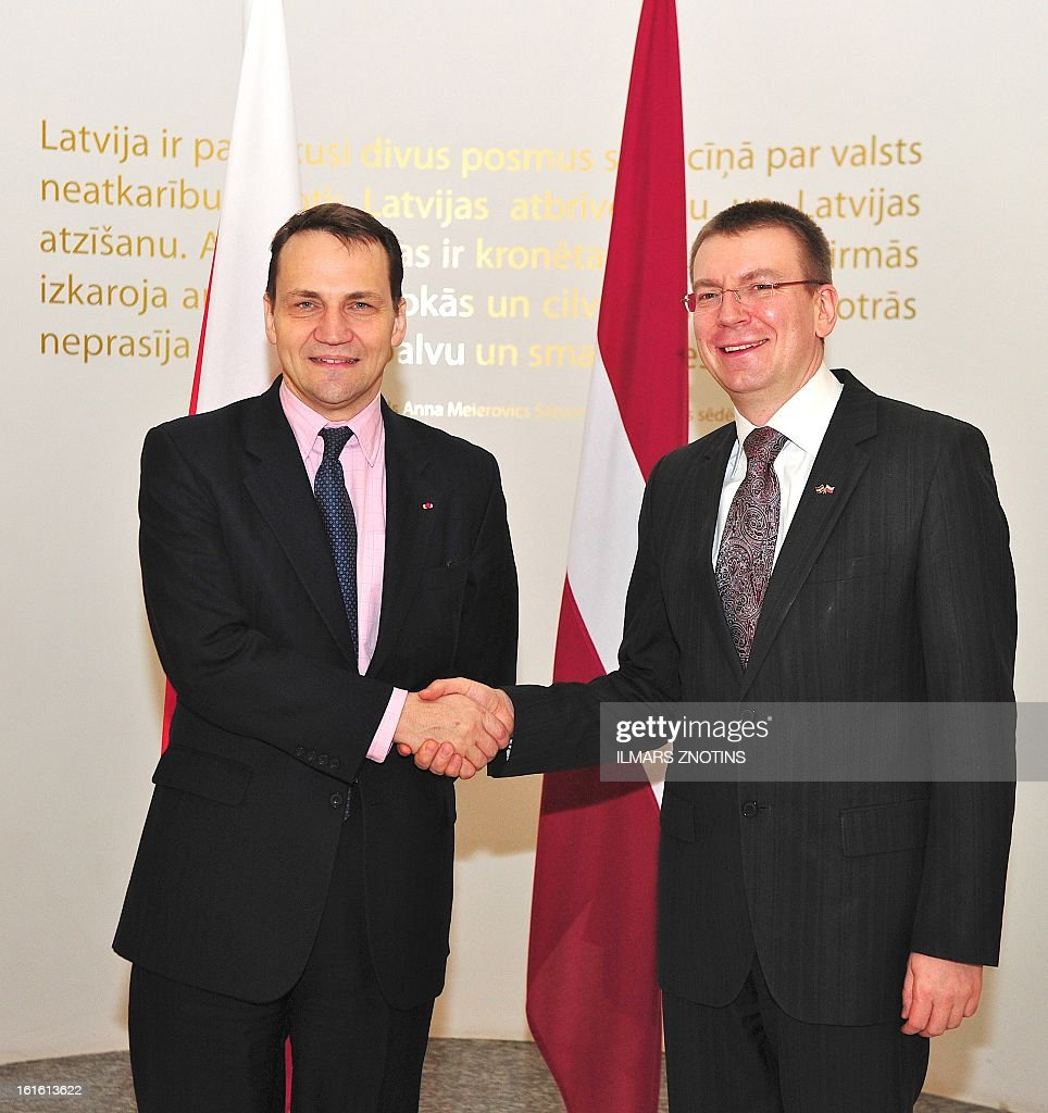 Latvian Foreign Minister Edgar Rinkevics (R) and his Polish counterpart Radoslaw Sikorski (L) shake hands prior to their meeting in Riga, Latvia on February 13, 2013. AFP PHOTO/ILMARS ZNOTINS