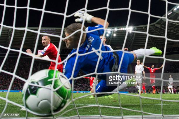 Latvian goalkeeper Andris Vanins concedes the first goal scored by Swiss midfielder Josip Drmic during the WC 2018 qualifying football match...
