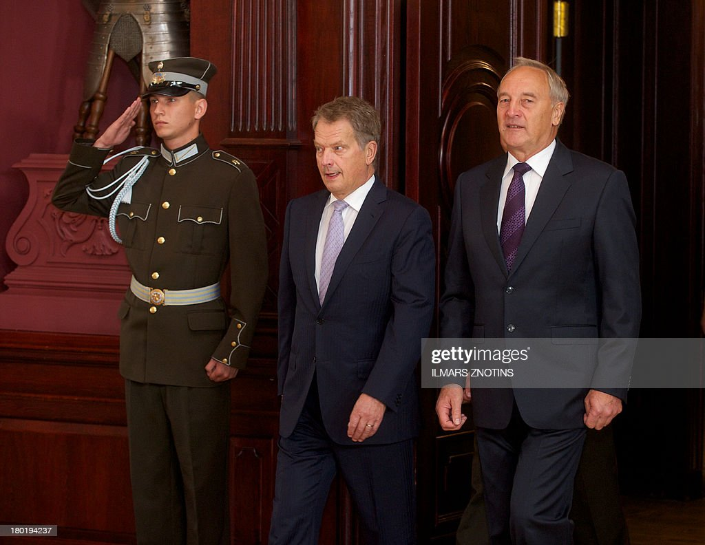 Latvian President Andris Berzins (R) and his Finish counterpart Sauli Niinisto (L) walk upon arrival in Riga, Latvia, on September 10, 2013 before their meeting.