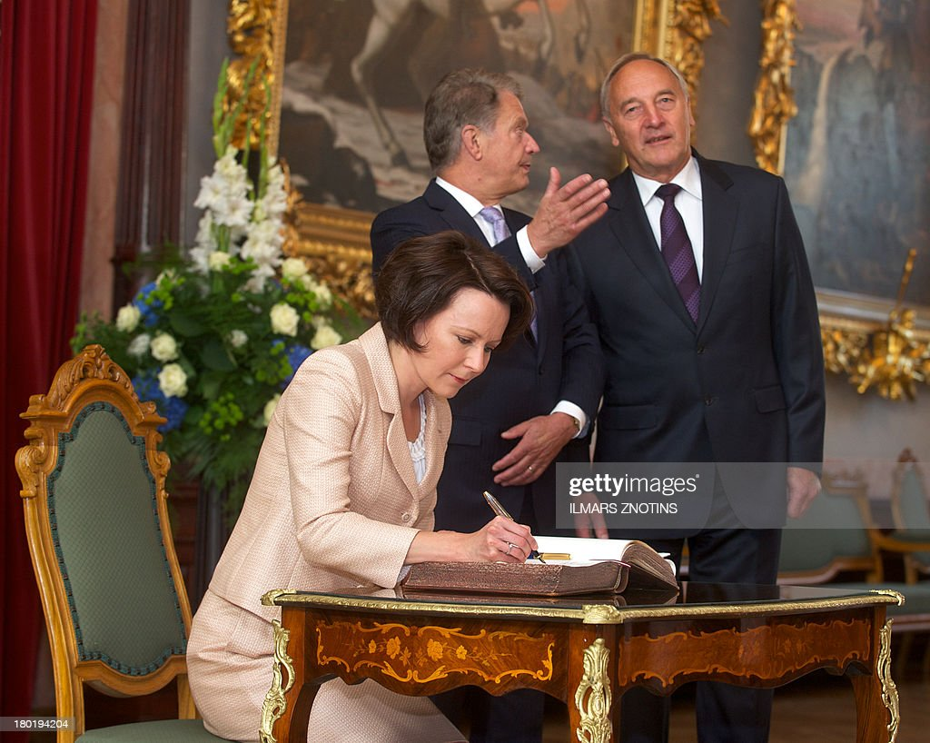 Latvian President Andris Berzins (R) chats with his Finish counterpart Sauli Niinisto (C) as Finish President's wife Jenni Haukio signs the guest book in Riga, Latvia, on September 10, 2013 before their meeting.