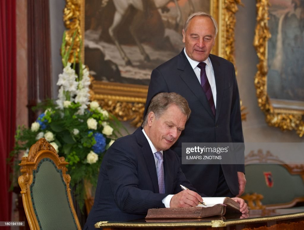 Latvian President Andris Berzins (R) looks on as his Finish counterpart Sauli Niinisto signs the guest book in Riga, Latvia, on September 10, 2013 before their meeting.