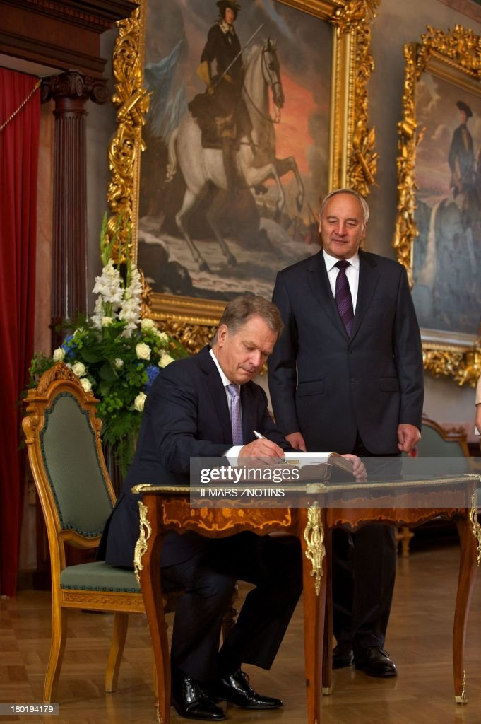 Latvian President Andris Berzins (R) looks on as his Finish counterpart Sauli Niinisto signs the guest book in Riga, Latvia, on September 10, 2013 before their meeting. AFP PHOTO / ILMARS ZNOTINS