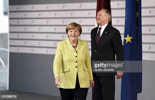 Latvian President Andris Berzins welcomes German chancellor Angela Merkel at the House of the Blackhead upon arrival for an informal dinner at the...