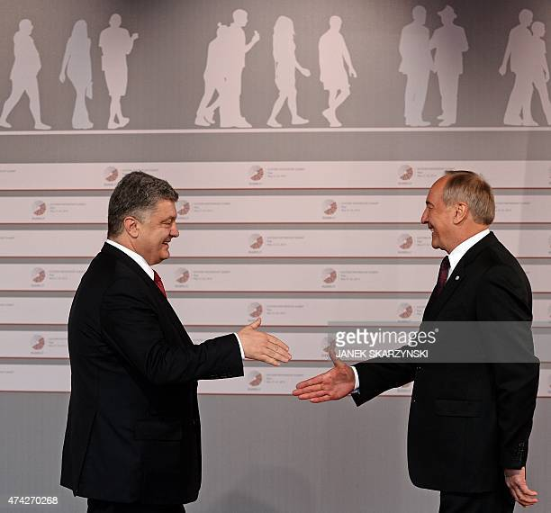 Latvian President Andris Berzins welcomes Ukrainian President Petro Poroshenko upon arrival at the House of the Blackhead upon arrival for an...
