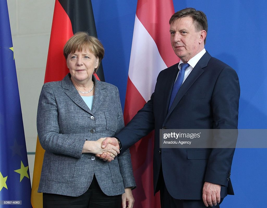 Latvian Prime Minister Maris Kucinskis (R) and German Chancellor Angela Merkel (L) shake hands as they pose for a photograph during a joint press conference after their talks in Berlin, Germany on April 29, 2016.