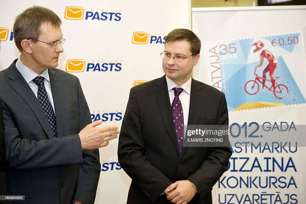 Latvian Prime Minister Valdis Dombrovskis (R) and Finance Minister Andris Vilks (L) stand in front of the mockup of a Latvian stamp denominated in both lats and euros during the stamp's presentation in Riga on January 30, 2013. Unfazed by the eurozone crisis, Latvia is poised to pass key legislation on January 31, 2013, paving the way for a request for EU approval of its entry as the zone's 18th member on January 1, 2014.