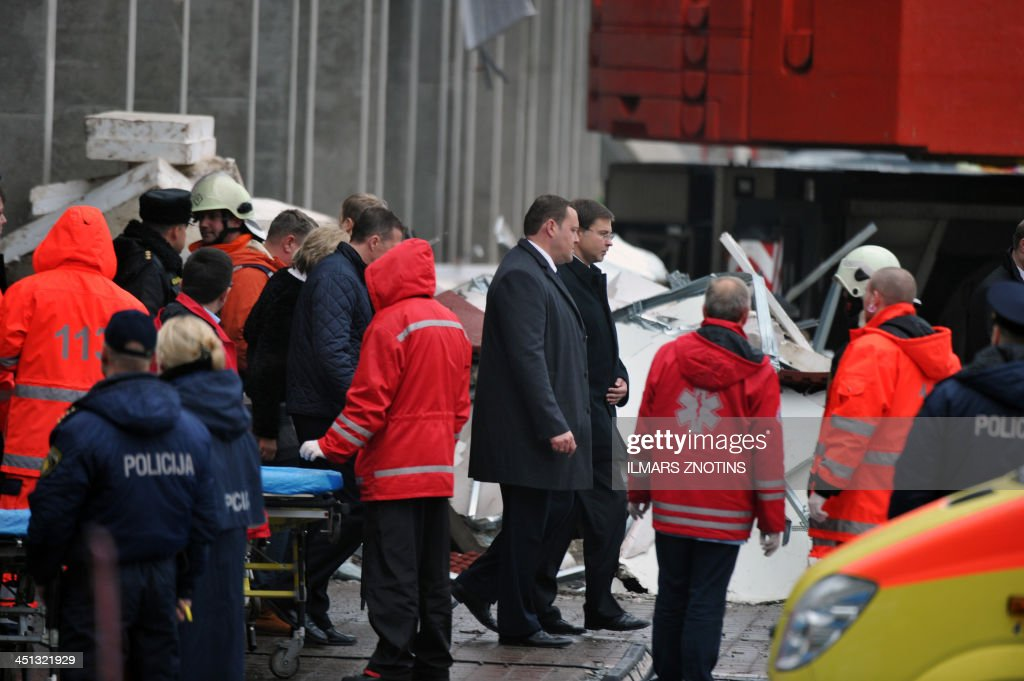 Latvian Prime Minister Valdis Dombrovskis (Centre R) and Interior Minister Rihards Kozlovskis visit the scene where the Maxima supermarket roof collapsed in Riga on November 22, 2013. Thirty three were killed and around 40 others injured when the roof of a supermarket collapsed a day earlier in a suburb of Latvia's capital Riga, emergency services said.