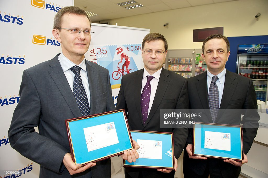 Latvian Prime Minister Valdis Dombrovskis (C), Finance Minister Andris Vilks (L) and Transport Minister Aivis Ronis (R) pose with Latvian stamps denominated in both lats and euros during the stamp's presentation in Riga on January 30, 2013. Unfazed by the eurozone crisis, Latvia is poised to pass key legislation on January 31, 2013, paving the way for a request for EU approval of its entry as the zone's 18th member on January 1, 2014.