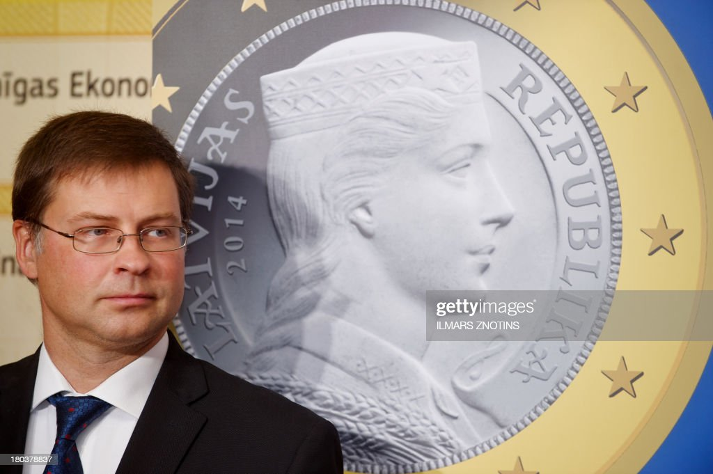 Latvian Prime Minister Valdis Dombrovskis stands in front of a picture of presented euro coins during th opening of the exhibition 'Euro-Our Currency' in Riga, Latvia, on September 12, 2013. Latvia replaces its current currency the lat with the euro in January 2012.