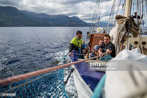 Latvians Andrejs Kirins and Armands Krastenbergs pull the rope as they set up a sail on the polish gaff schooner Kapitan Borchardt as they take part...