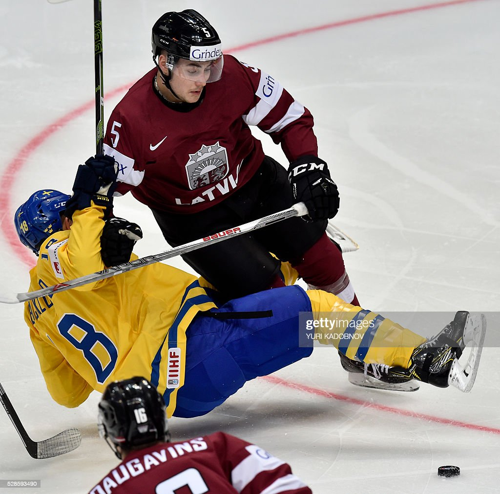 Latvia's defender Edgars Siksna (R) vies for a puck with Sweden's forward Mikael Backlund during the group A preliminary round game Sweden vs Latvia at the 2016 IIHF Ice Hockey World Championship in Moscow on May 6, 2016. / AFP / YURI