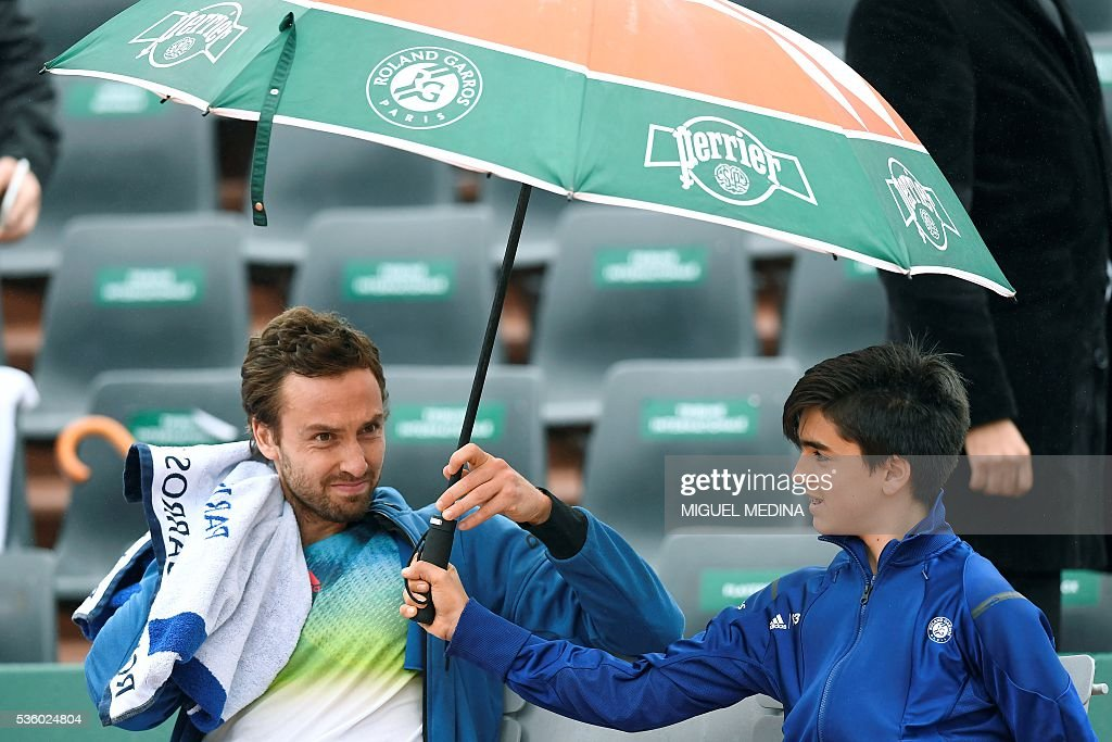 Latvia's Ernests Gulbis sits under an umbrella as play is interrupted due to rain during his men's fourth round match against Belgium's David Goffin at the Roland Garros 2016 French Tennis Open in Paris on May 31, 2016. / AFP / MIGUEL