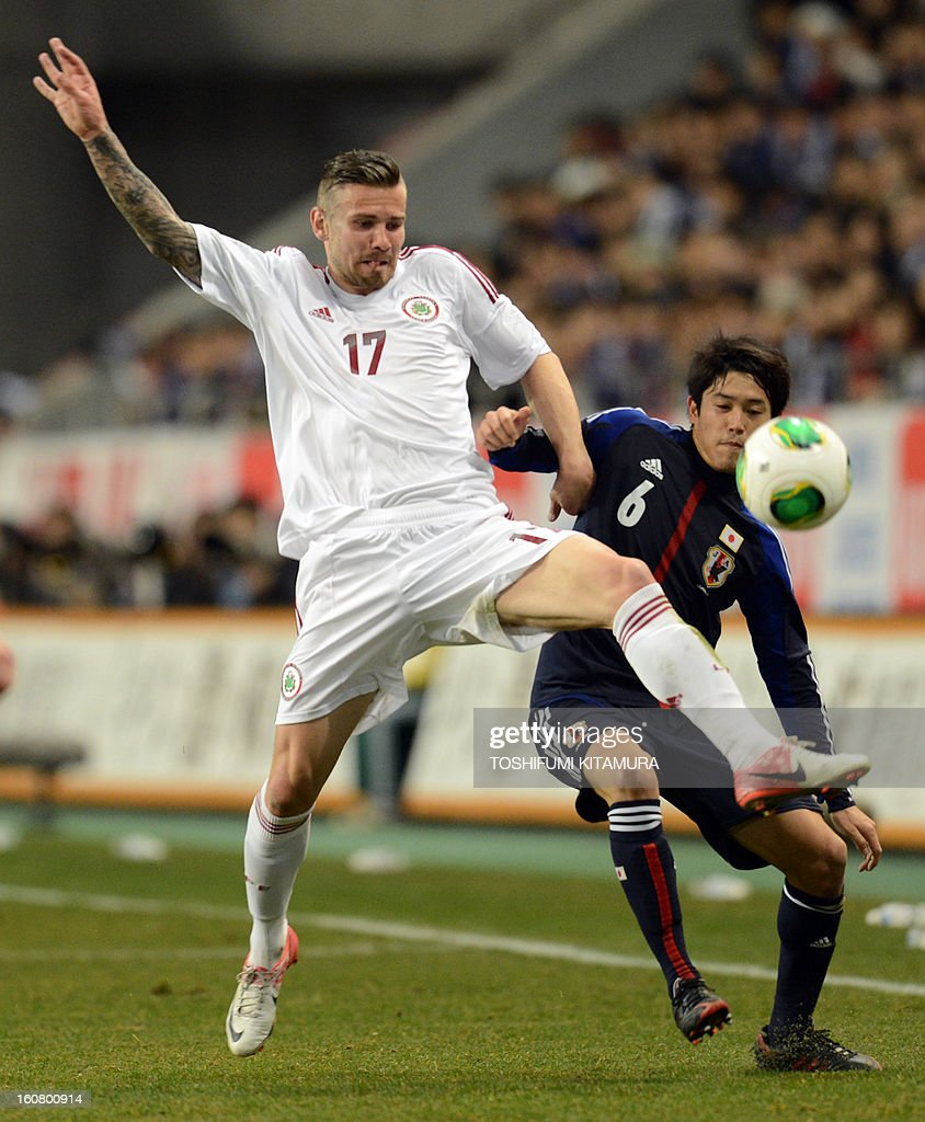 Latvia's forward Edgars Gauracs (L) fights for the ball with Japan's defender Atsuto Uchida (R) during their friendly match in Kobe on February 6, 2013.