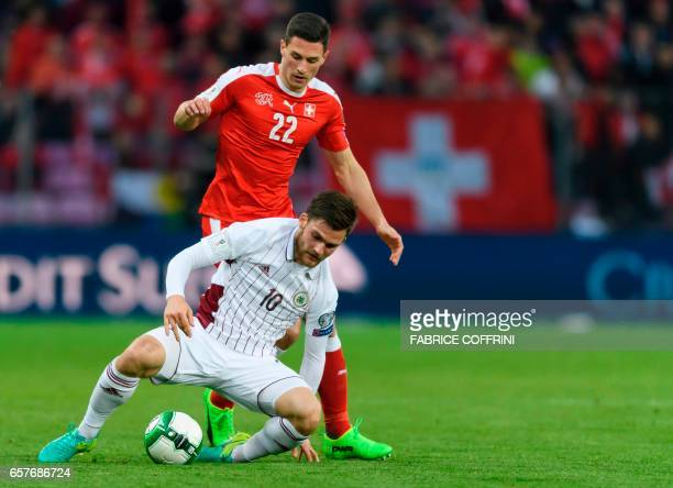 Latvia's forward Valerijs Sabala vies with Swiss defender Fabian Schar during the WC 2018 qualifying football match Switzerland vs Latvia on March 25...