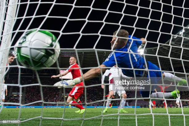 Latvia's goalkeeper Andris Vanins fails to stop the first goal scored by Swiss midfielder Josip Drmic during the WC 2018 qualifying football match...