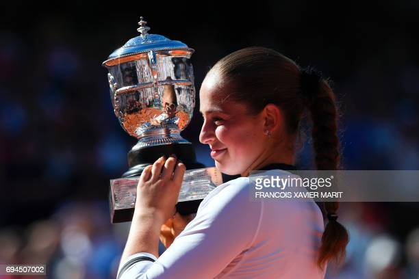 TOPSHOT Latvia's Jelena Ostapenko celebrates with her trophy after winning her final tennis match against Romania's Simona Halep at the Roland Garros...
