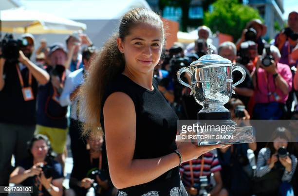 Latvia's Jelena Ostapenko poses on June 11 2017 with her trophy after winning her final tennis match against Romania's Simona Halep on June 10 at the...
