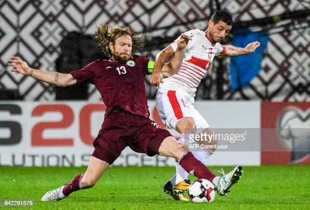 Latvia's Kaspars Gorkss fights for the ball with Switzerland's Blerim Dzemaili during the WC2018 group B qualifying football match between Latvia and...