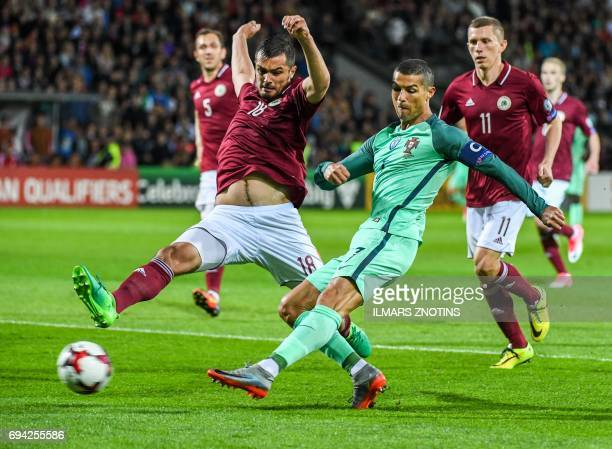 Latvia's Nikita Kolesovs vies with Portugal's Cristiano Ronaldo during the FIFA World Cup 2018 qualification football match between Latvia and...