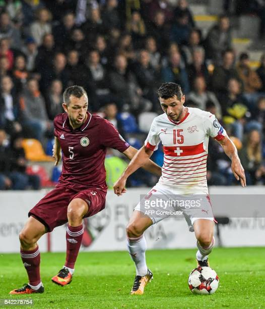 Latvia's Olegs Laizans fights for the ball with Switzerland's Blerim Dzemaili during the WC2018 group B qualifying football match between Latvia and...